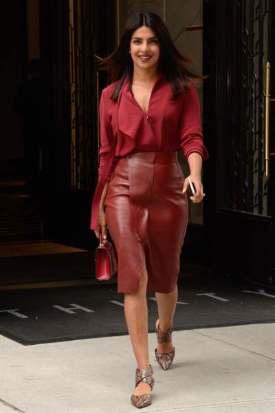 Priyanka Chopra opte pour un total look rouge, jupe en cuir, chemisier et sac, comme son amie Meghan Markle.