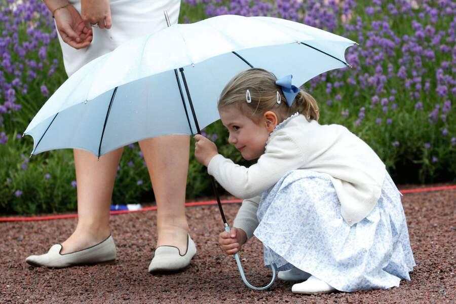 Alors que sa maman fête son anniv, Estelle, 4 ans,  joue à cache-cache, aux pieds de Katie, sa nounou