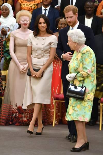 """Meghan Markle en robe Prada, avec le prince Harry et la reine Élisabeth II, aux """"Queen's Young Leaders Awards"""" 2018"""