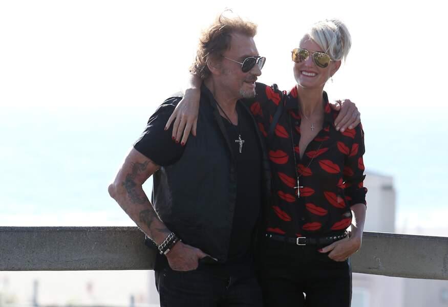 Johnny au bras de Laeticia à Los Angeles en 2014. Sur son bras droit, on aperçoit son tatouage dédié à Jade et Joy