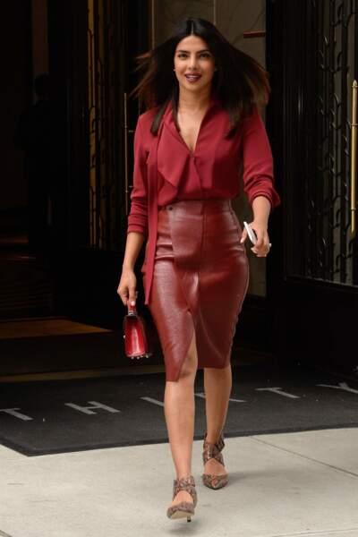 Priyanka Chopra s'inspire de Meghan Markle pour un total look rouge, jupe en cuir et chemisier vaporeux.