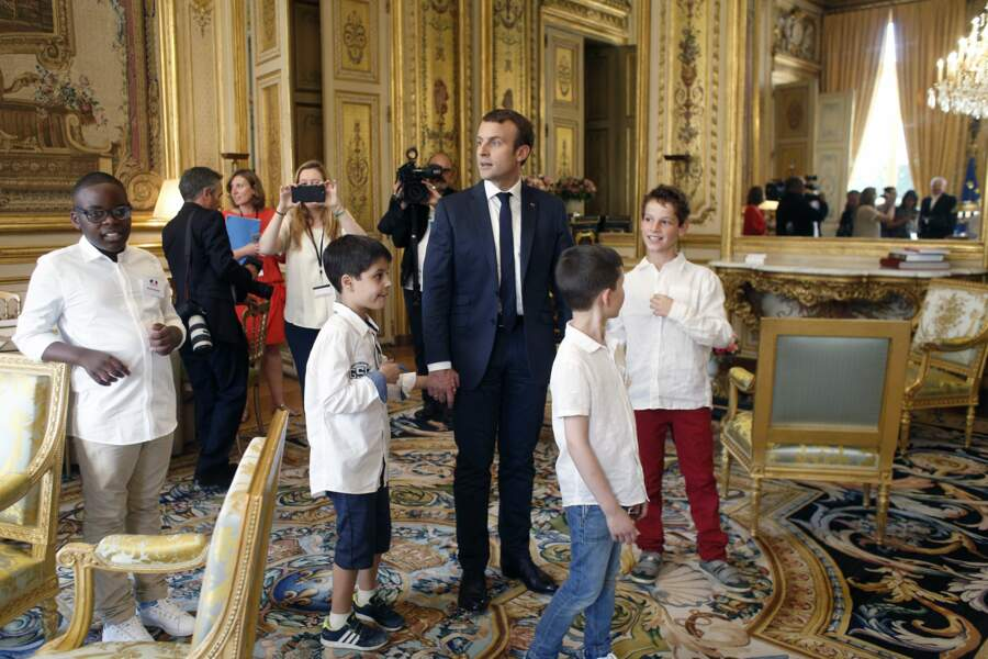 Les enfants tiennent la main d'Emmanuel Macron et passent dans des salons luxueux...