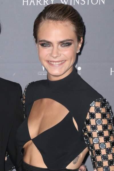 Cara Delevingne très souriante avec un maquillage très fort sur les yeux et un wet-hair canon