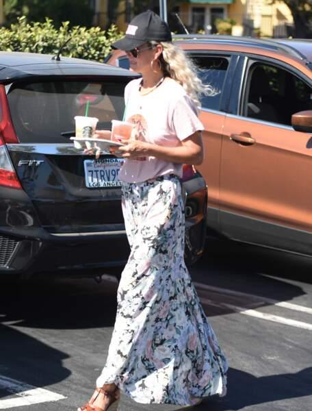 Laeticia Hallyday en jupe longue fleurie et casquette stylée