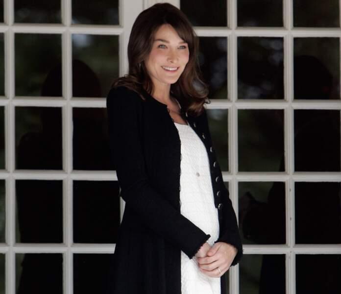 Alors enceinte de Giulia, elle affiche un leger baby bump en robe blanche et longue veste noire à Deauville en 2011