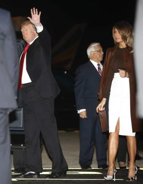 Melania Trump en jupe blanche ouverte et long manteau en cuir