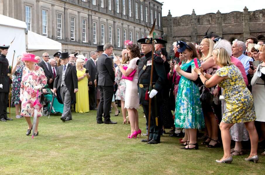 Les convives prennent en photo Elizabeth II lors de la garden party qui a eu lieu au palais de Holyroodhouse à Edim