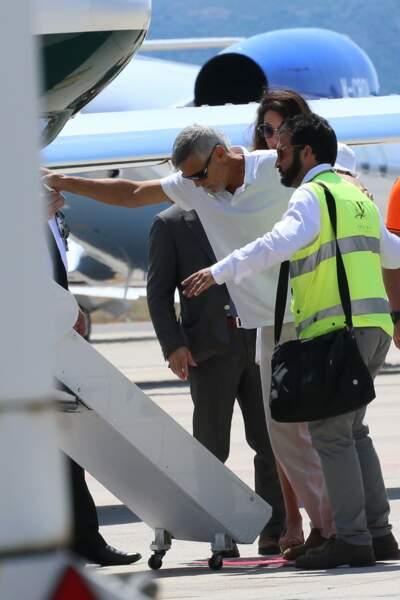 George Clooney semble tout de même avoir besoin du personnel au sol pour l'aider à monter à bord de l'avion.