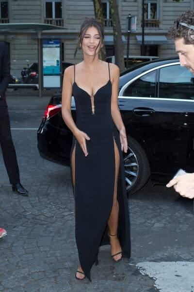 Emily Ratajkowski portait une robe noire longue, fendue sur les deux cuisses, et maxi décolletée
