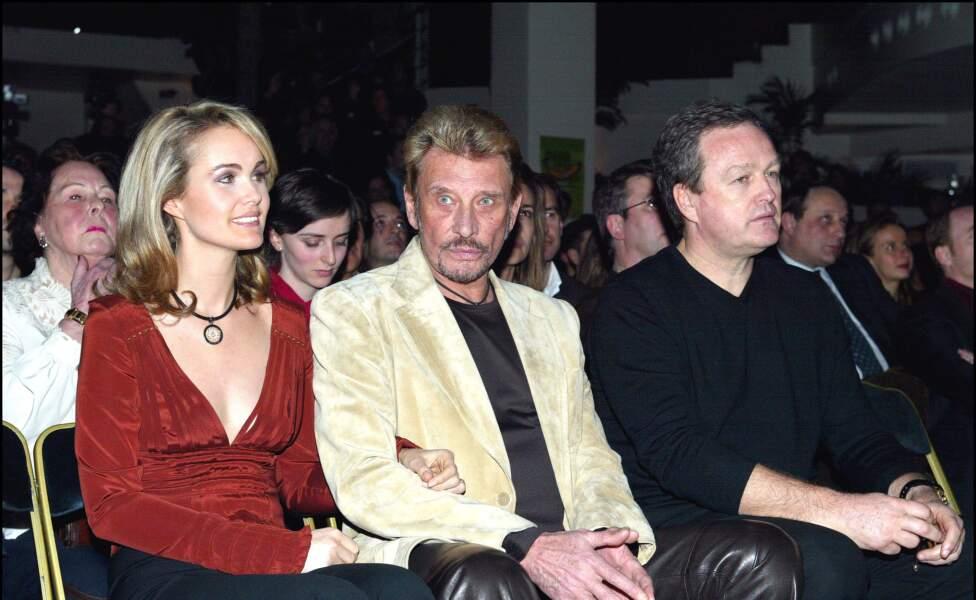 """Laeticia et Johnny Hallyday aux côtés d'André Boudou lors de la soirée """"Humour et pub"""" à l'Amnésia en 2004."""