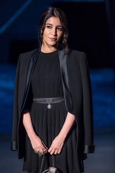 Leïla Bekhti, très chic en veste de smoking et jupe plissée noire lors du défilé Croisière au Grand Palais à Paris
