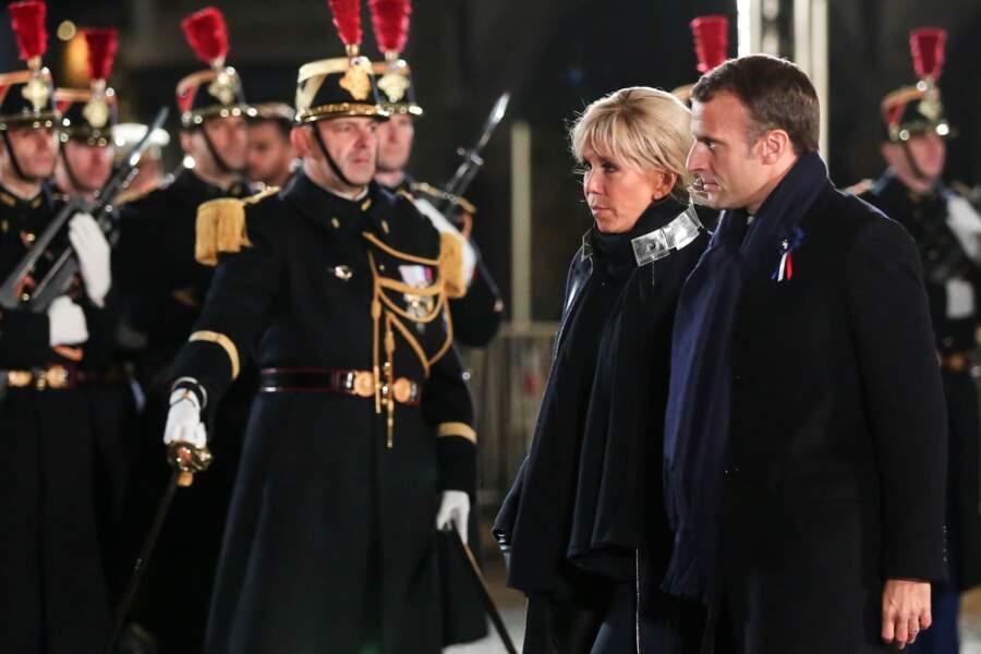 Le manteau de Brigitte Macron est très original : un liseré métallique est cousu sur l'extérieur d'un col officier.