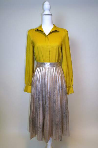 Une jupe métallisée et une chemise jaune en soie sont en vente dans le dressing de Jenifer.