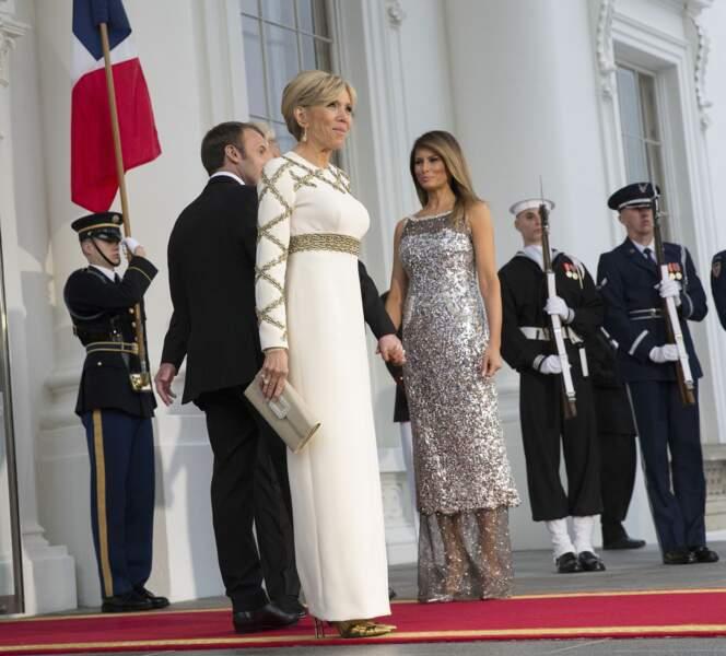 Brigitte Macron en robe de vestale blanche et dorée Louis Vuitton face à Melania Trump le 24 avril 2018