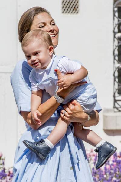 Le prince Oscar dans les bras de sa mère, la princesse Victoria de Suède au château de Solliden, sur l'ïle d'Öland.