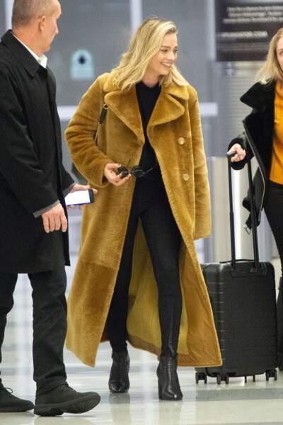 Margot Robbie ose le grand manteau en fausse fourrure jaune avec un total look noir.