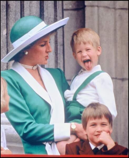 """Harry fait une grimace dans les bras de Diana, à côté de William, lors de la parade """"Trooping The Colour"""" en 1988"""
