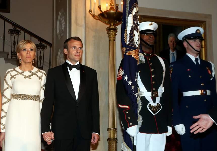 Brigitte Macron en robe de vestale face à Melania Trump en robe Chanel scintillante