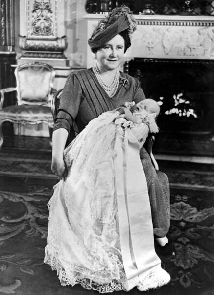 La reine mère tenant dans ses bras son petit-fils le prince Charles lors de son baptême, le 15 décembre 1948