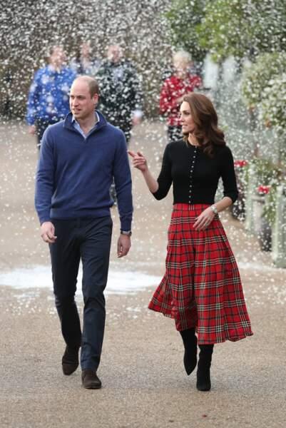 Kate Middleton en rouge et noir entre jupe écossaise, bottes et top noirs