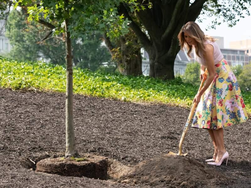 Melania plante un arbre en jupe fleurie Valentino et escarpins Louboutin, le 28 août 2018 à la Maison Blanche
