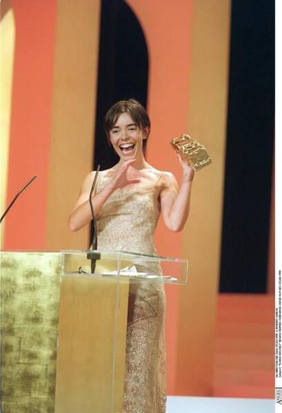 """Elodie Bouchez, en robe longue dorée à fines bretelles, reçoit le César pour """"La Vie rêvée des anges"""" (1999)"""