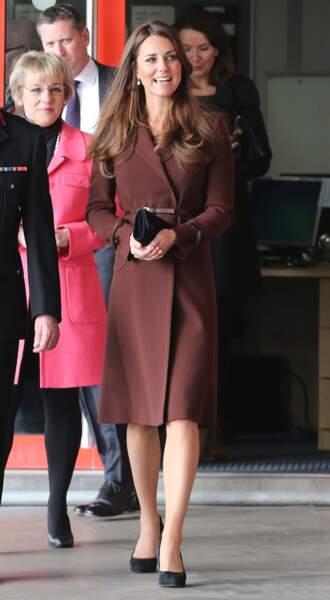 Kate Middleton, enceinte de 5 mois, dissimulant son ventre avec une pochette, à Grimsby, le 5 mars 2013.