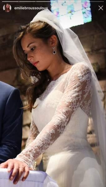 La jeune femme portait une élégante robe de mariée et un voile dont sa chevelure sortait en cascade.
