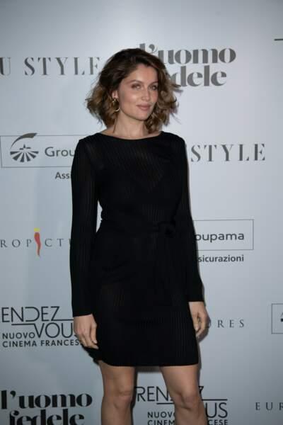 Laetitia Casta rayonnante avec un carré bouclé et une robe noire moulante et courte