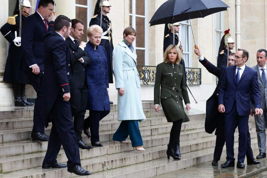 Brigitte Macron en manteau d'officier Louis Vuitton et bottines à talons