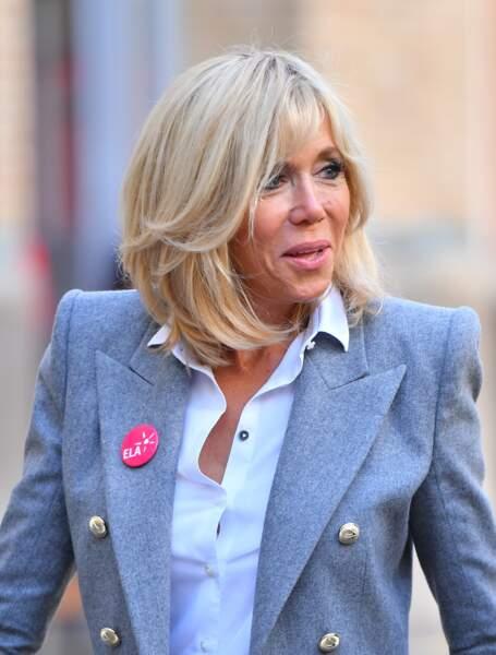 Brigitte Macron, carré blond, chemise blanche ouverte et blazer gris, sa panoplie parfaite