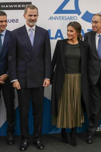 La jupe dorée de Letizia d'Espagne est portée avec des talons mats noirs et une veste noire portée sur les épaules.