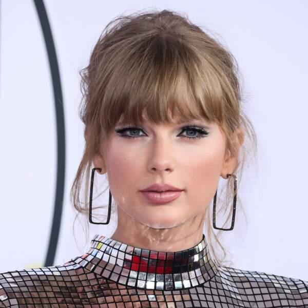 Très chic blond foncé pour Taylor Swift, sublimé par une frange épaisse