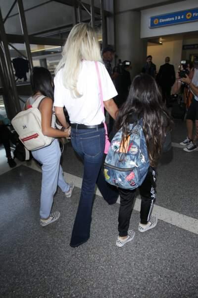 """Laeticia Hallyday quitte Los Angeles pour Paris avec ses deux filles. Détail : le """"JH"""" sur le sac à dos de Jade"""