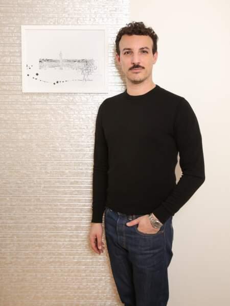 L'artiste Nicolas Ouchenir posant devant un de ses dessins