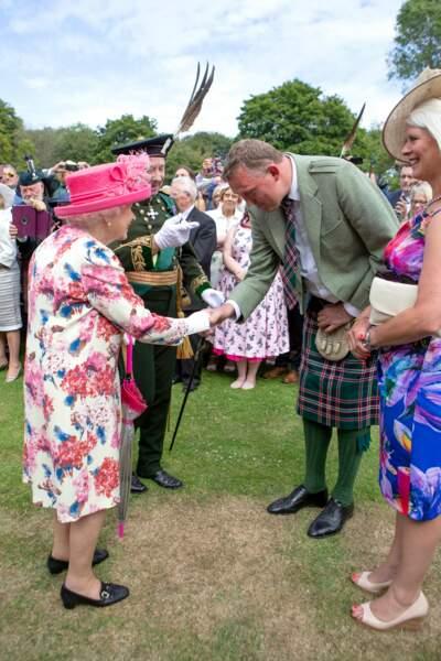 La reine Elizabeth II salue l'un des convives de la garden party du palais de Holyroodhouse à Edimbourg
