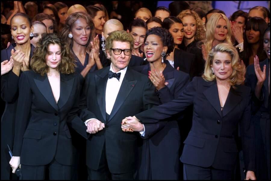 En 2002, le dernier défilé de Mr Saint Laurent entouré de ses muses en smoking, Laetitia Casta et Catherine Deneuve