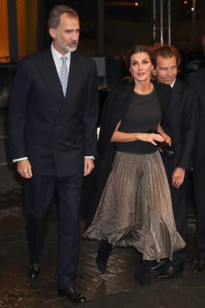 Jupe plissée dorée et haut noir à col rond, la reine Letizia d'Espagne est à 100 % dans la tendance.