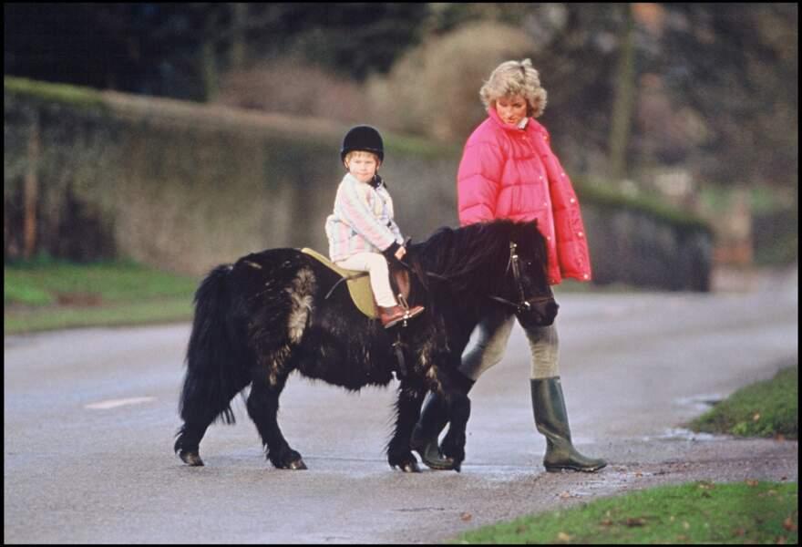 La prince Harry fait du poney, accompagné par sa mère Lady Diana, en 1988