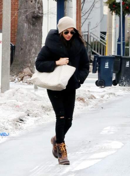Pour des looks incognito, Meghan Markle opte pour une doudoune noire XXL avec un slim et on sac Goyard crème.