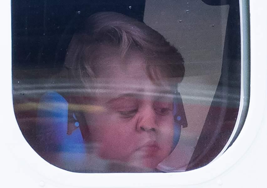 Le nez écrasé sur la vitre de l'avion, le petit prince George observe la piste de décollage