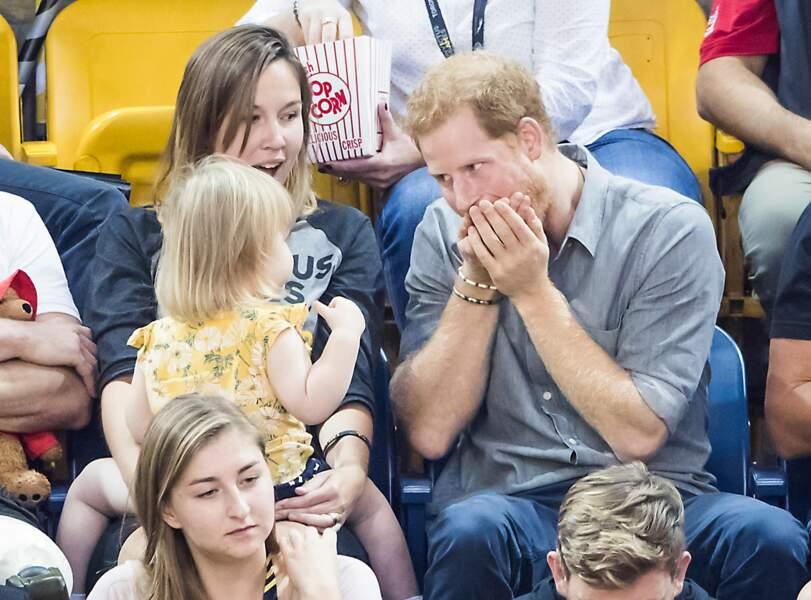 Le prince Harry fait le clown avec une petite fille en plein match