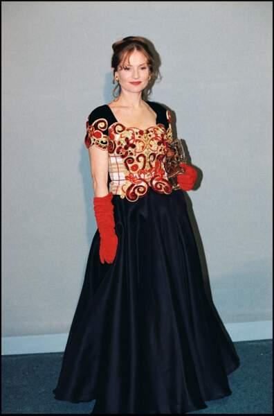 """Isabelle Huppert, en robe à corset rouge et or, reçoit le César pour """"La Cérémonie"""" en 1996"""