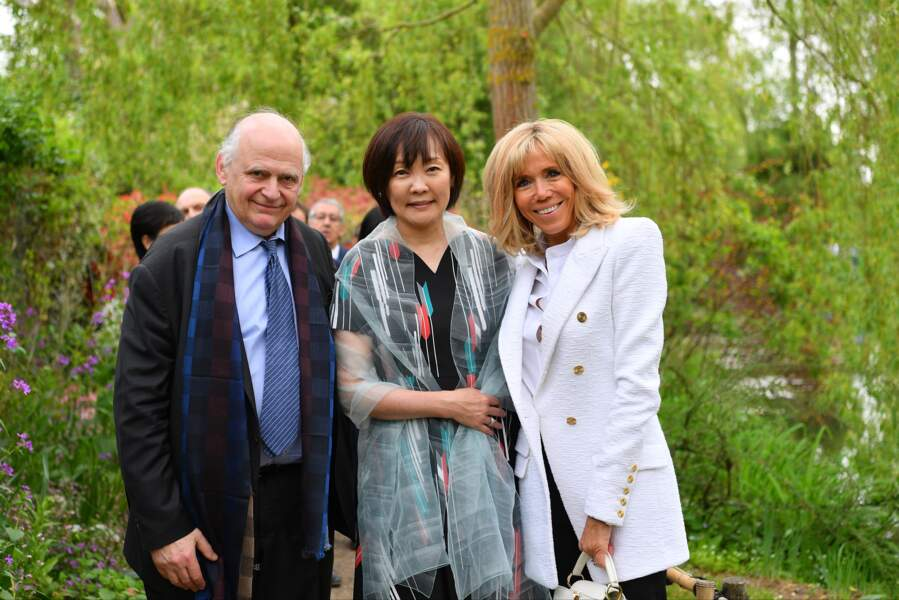 Brigitte Macron ultra chic avec un sac blanc Louis Vuitton, une veste longue blanche et un carré blond tendance