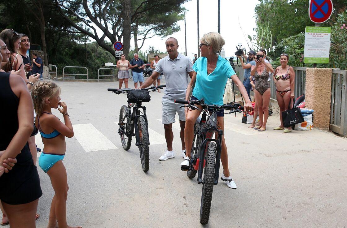 La Première dame Brigitte Macron se promène en vélo au Fort de Brégançon avec ses gardes du corps.