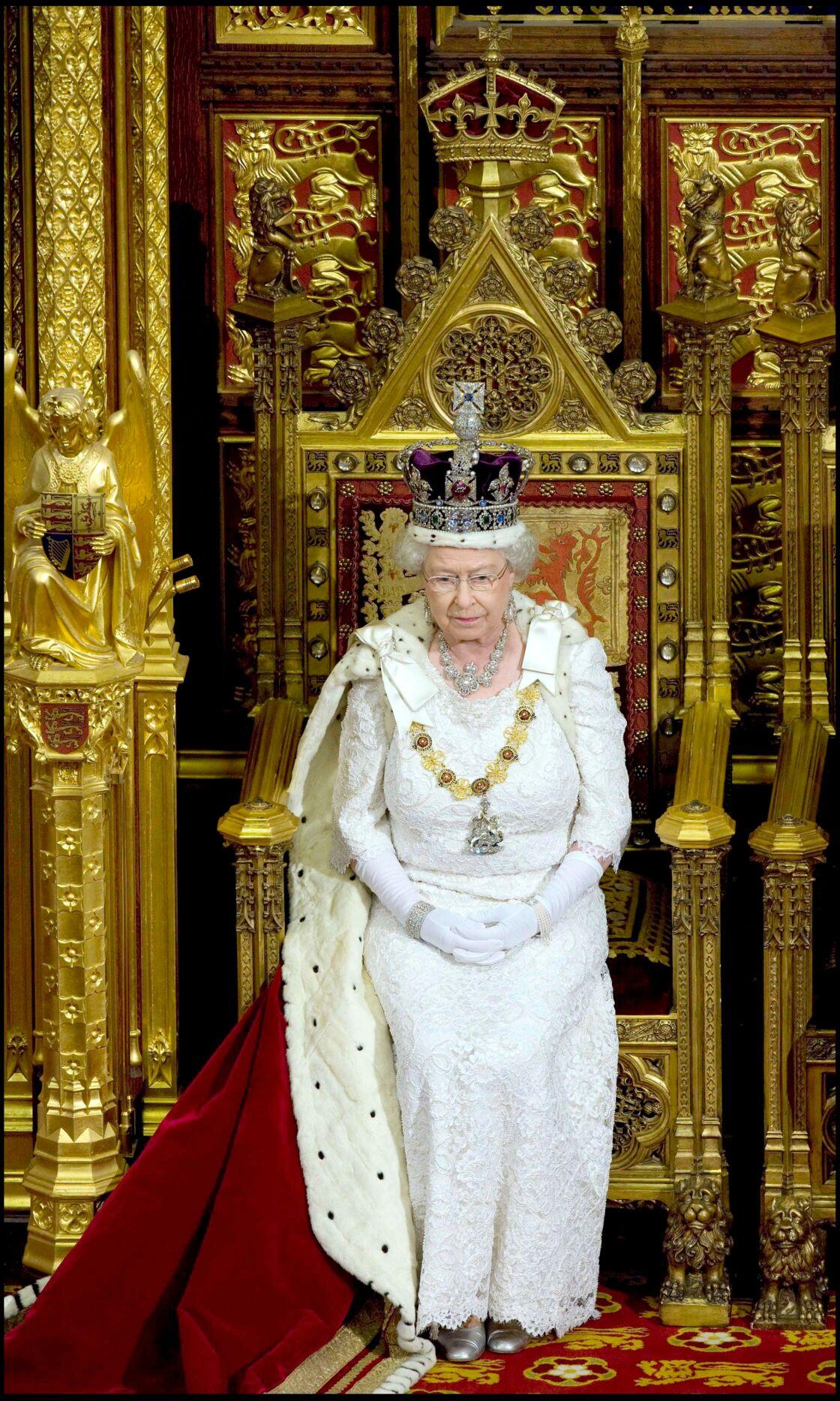 Elizabeth II, assise dans le trône que les époux de Cholmondeley gardent dans leur manoir du Norfolk, entre deux ouvertures du Parlement.