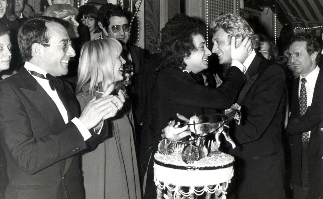 Johnny dans les bras de Michel Sardou, lors de l'anniversaire de mariage de ce dernier avec sa femme Babette, à Paris, le 25 janvier 1978.