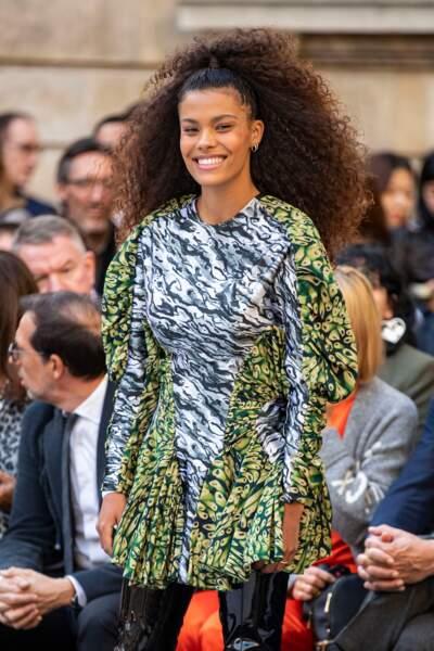 Tina Kunakey, chevelure bouclée sublime coiffée en demi-queue de cheval pour le défilé l'Oréal Paris