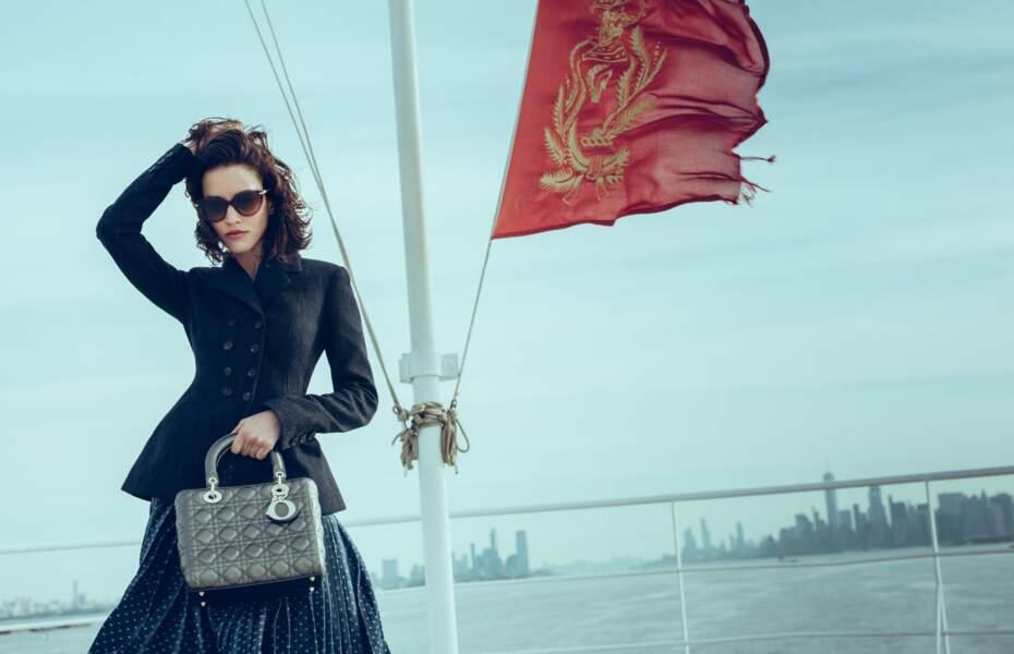 Veste en laine à rayures, jupe en denim à pois, sac en cuir, l'ensemble Dior. Lunettes de soleil Bulgari.