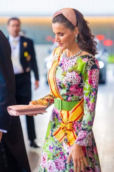 Côté accessoire, Sa Majesté portait un headband Nana Golmar, un collier Ansorena, ainsi qu'une pochette rose pâle Carolina Herrera.